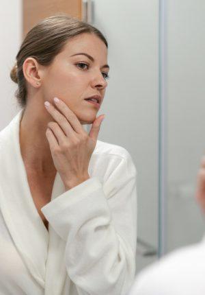 Skin and Immunity Blog Photo - Woman in Bathrobe Looking at Face