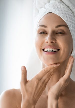 Epidermal Turnover - Happy lady look in bathroom mirror touching healthy face skin